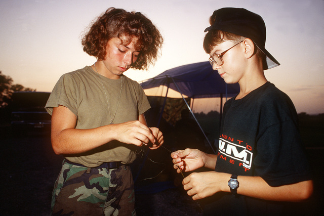 SENIOR AIRMAN Theresa Sronce of the 182nd Fighter Group, Peoria, Illinois and Branden Myers a local, rig a fishing pole to try their luck in the Mississippi River