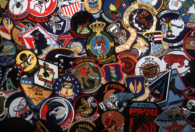 A close-up view of Air Force patches exhibiting the symbols and names of their respective military units.