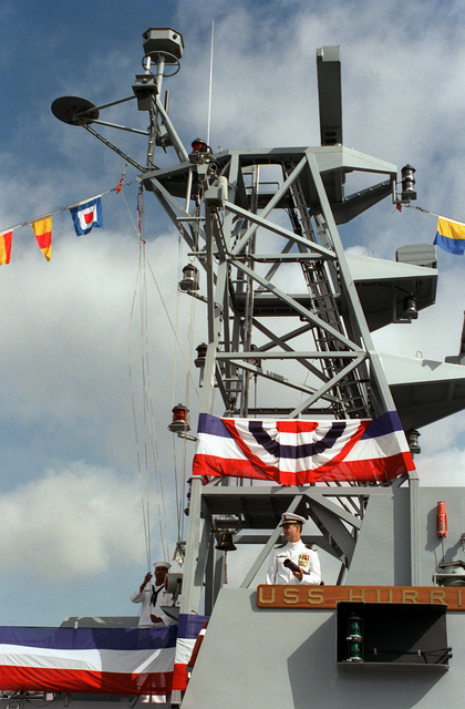 As the officer of the watch stands by on the bridge wing of the Cyclone class patrol craft USS HURRICANE (PC-3) the signalman hoist the commissioning pennant up the yard arm and completes the commissiong of the vessel. The ceremony took place at the Naval Air Station North Island pier