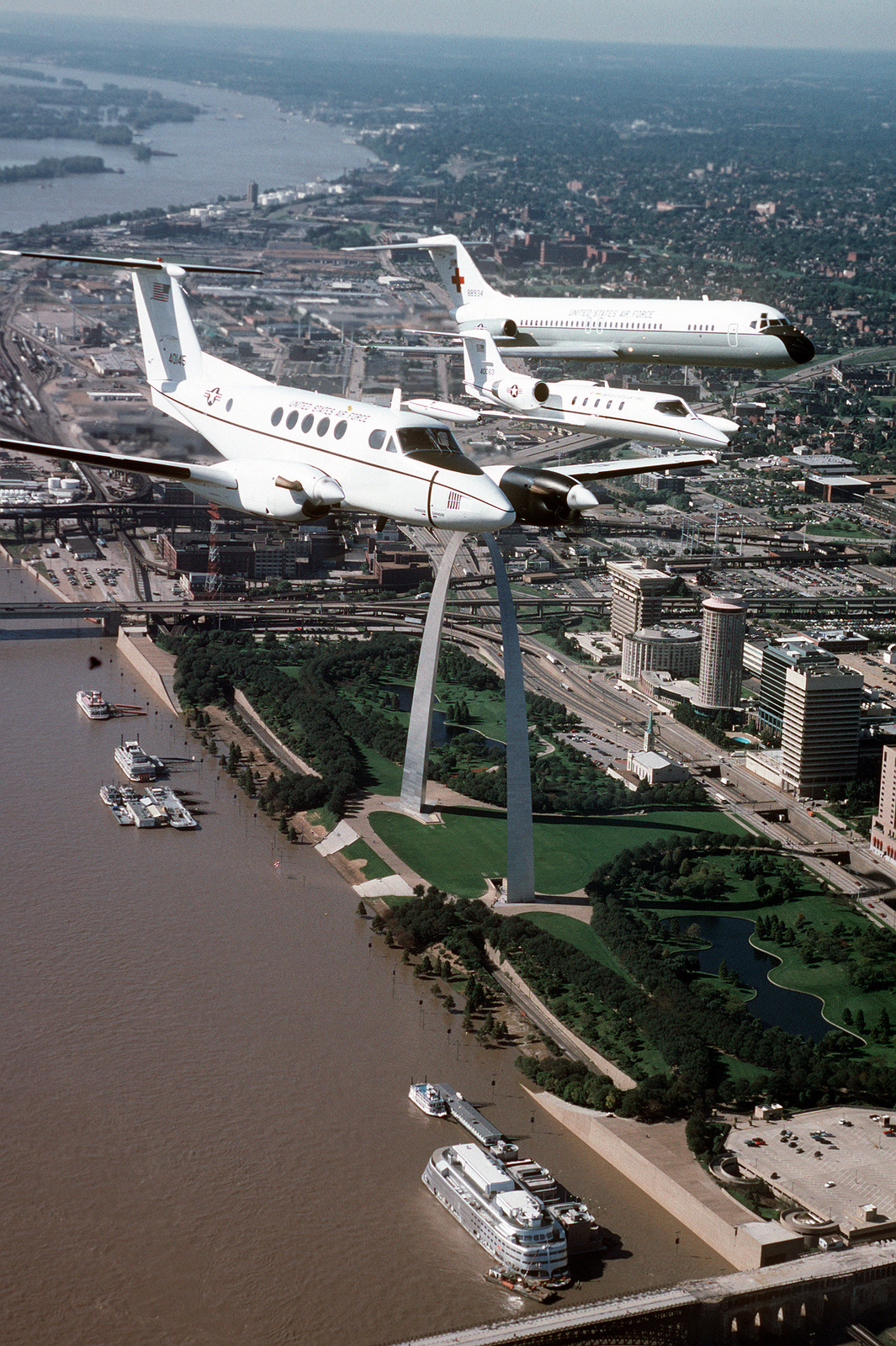 An air-to-air, three quarter front view of a Beech Aircraft built C-12F with a Lear Jet built C-21A and a McDonnell Douglas-built C-9A Nightingale aircraft, flying off the left wing of the C-12F. All aircraft are from the 375th Airlift Wing, Air Mobility Command and are flying over the St. Louis Arch, on the banks of the Mississippi River, and Busch stadium during a training mission