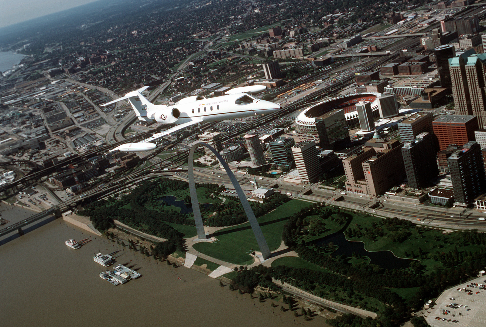 An air-to-air, three quarter front view of a Lear Jet-built C-21A aircraft during a flight over the famous St. Louis Arch, on the banks of the Mississippi River, and Busch stadium. The C-21A is assigned to the 375th Airlift Wing, Air Mobility Command