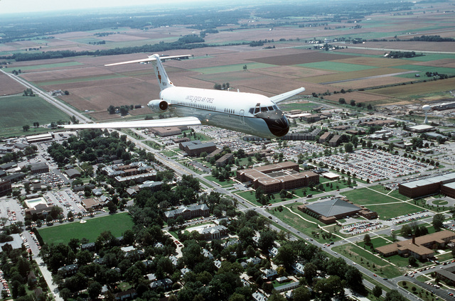 An air-to-air, three quarter front view of a McDonnell Douglas built C-9A Nightingale aircraft flying over the main part of the base and the HQ Air Mobility Command building. The C-9A is assigned to the 375th Airlift Wing, Air Mobility Command