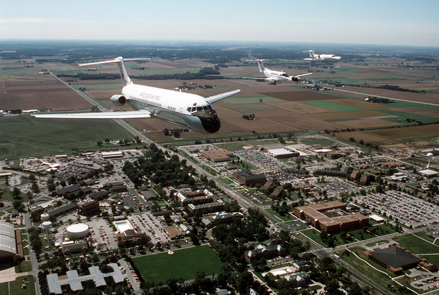 An air-to-air, three quarter front view of a McDonnell Douglas built C-9A Nightingale aircraft leading a formation that includes a C-12F and a C-21A over the main part of the base and the HQ Air Mobility Command building. All aircraft are assigned to the 375th Airlift Wing, Air Mobility Command