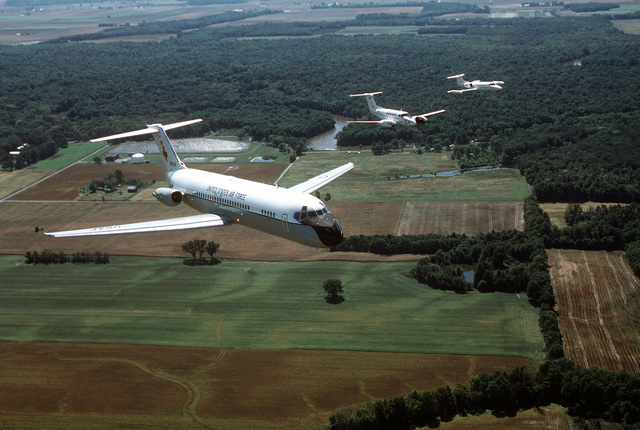 An air-to-air, three quarter front view of a McDonnell Douglas built C-9A Nightingale aircraft leading a formation that includes a C-12F and a C-21A over the farmland near the base. All aircraft are assigned to the 375th Airlift Wing, Air Mobility Command