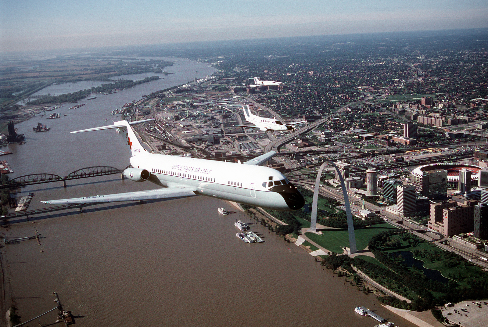 An air-to-air, three quarter front view of a McDonnell Douglas-built C-9A Nightingale aircraft leading a formation that includes a Beech Aircraft built C-12F and a Lear Jet built C-21A. The training flight is over the famous St. Louis Arch along the banks of the Mississippi River. All aircraft are from the 375th Airlift Wing, Air Mobility Command