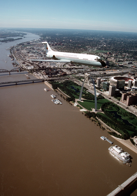 An air-to-air, three quarter front view of a McDonnell Douglas-built C-9A Nightingale aircraft during a flight over the famous St. Louis Arch, on the banks of the Mississippi River, and Busch stadium. The C-9A is assigned to the 375th Airlift Wing, Air Mobility Command