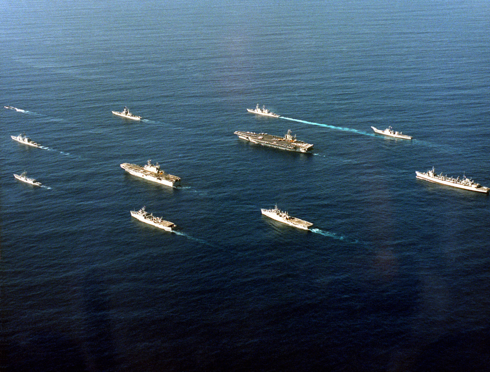 The Battle Group built around the nuclear-powered aircraft carrier USS CARL VINSON (CVN-70) steams towards a naval operational training are off the southern California coast. The ships are, (clockwise from the lower left), the guided missile frigate USS REUBEN JAMES (FFG-57), guided missile cruiser USS ANTIETAM (CG-54), nuclear-powered attack submarine USS ASHEVILLE (SSN-758), nuclear-powered guided missile cruiser USS ARKANSAS (CGN-41), destroyer USS HEWITT (DD-988), fast combat support sh USS CAMDEN (AOE-2), amphibious assault ship USS PELELIU (LHA-5) & 3 unidentified amphibious ships