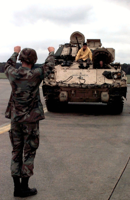 A member of the 24th Infantry Division, Fort Stewart, Georgia, stands back to camera and uses hand signals to line up a US Army M2A2 Bradley Fighting Vehicle before it is loaded onto a US Air Force C-5B Galaxy (not shown). The Army vehicle will be flown to Mogadishu, Somalia in support of Operation Restore Hope