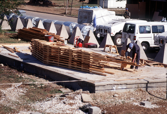 A Macedonian carpenter prepares the framework that will support the roof of the recreation center