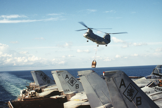 A CH-46D/E Sea Knight helicopter of Helicopter Squadron 11 (HS-11) transports supplies from the combat stores ship USNS SIRIUS (T-AFS-8) to the flight deck of the aircraft carrier USS AMERICA (CV-66) during a vertical replenishment operation as the carrier is operating in support of Operation Deny Flight. In the foreground several F-14 Tomcat aircraft of Fighter Squadron 102 (FV-102) are parked at the edge of the flight deck