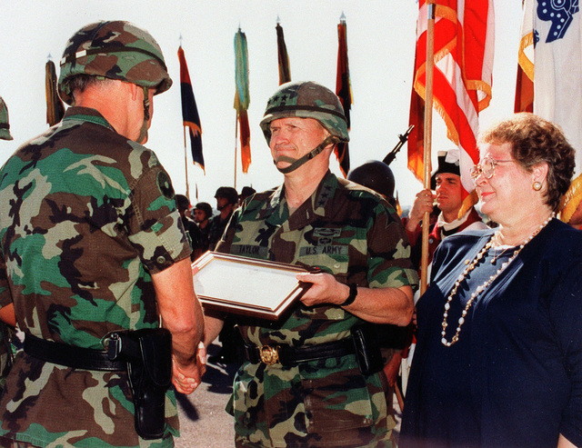 Forces Command (FORSCOM) Commander, General Dennis J. Reimer, presents the Distinguished Service Medal to Lieutenant General Horace G. Taylor during his retirement and change of command ceremony. LT. GEN. Taylor's wife, Mary Jane Taylor looks on