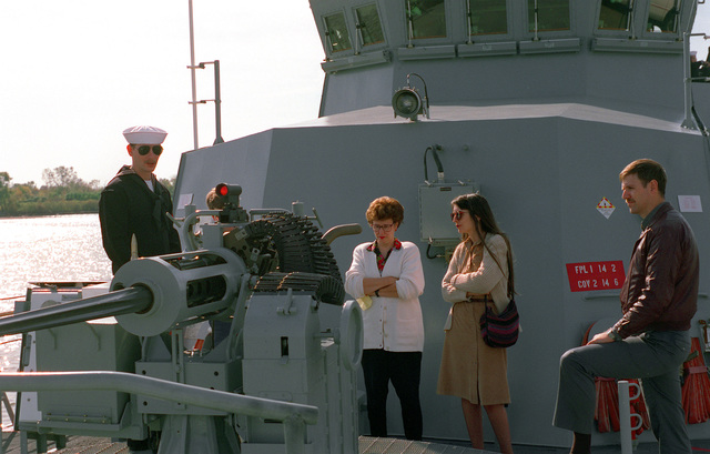 Quartermaster 3rd Class Michael Colby explains the operation of the bow-mounted Mark 38 25mm gun aboard the coastal patrol ship USS TEMPEST (PC-2) while the ship is open for public tours at the Washington Navy Yard. Looking on are Still Media Records Center employees Barbara Proffitt, left, and Judy Zukoski