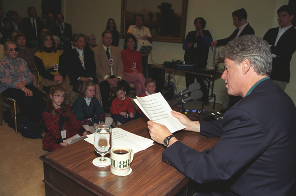 Photograph of President William J. Clinton Delivering the Weekly Radio Address in the Oval Office at the White House