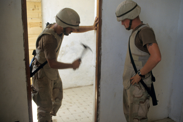 SPC. Matthews and PVT. Higgins of the 96th Civil Affairs Company, put in a door frame at a Somali school in support of UNOSOM II