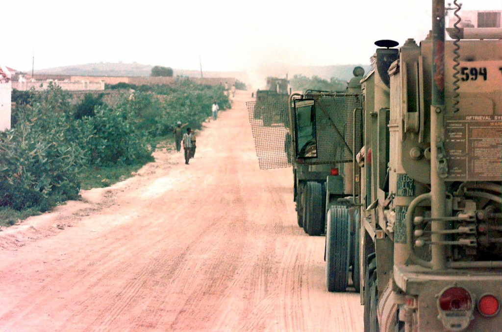 A left side rear view of a row of US Army M915 Series Tractors lined up along the side of the road. They are from the 594th Transportation Company, Fort Campbell, Kentucky, and are at Rabbit Base, which is the Indian troop's base camp next to Mogadishu airport. The tractors will hook up to Indian trailers and move them to the new Indian camp at Baidoa, Somalia. This mission is in direct support of Operation Restore Hope