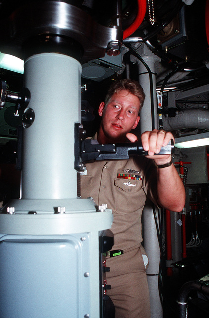 At the spotting periscope of the ballistic missile submarine USS NEBRASKA (SSBN-739) CHIEF Fire Control Technician (Guns) (FTGC) Stephen J. Ford keeps an eye for surface traffic as the ship puts to sea from Port Canaveral, Fla