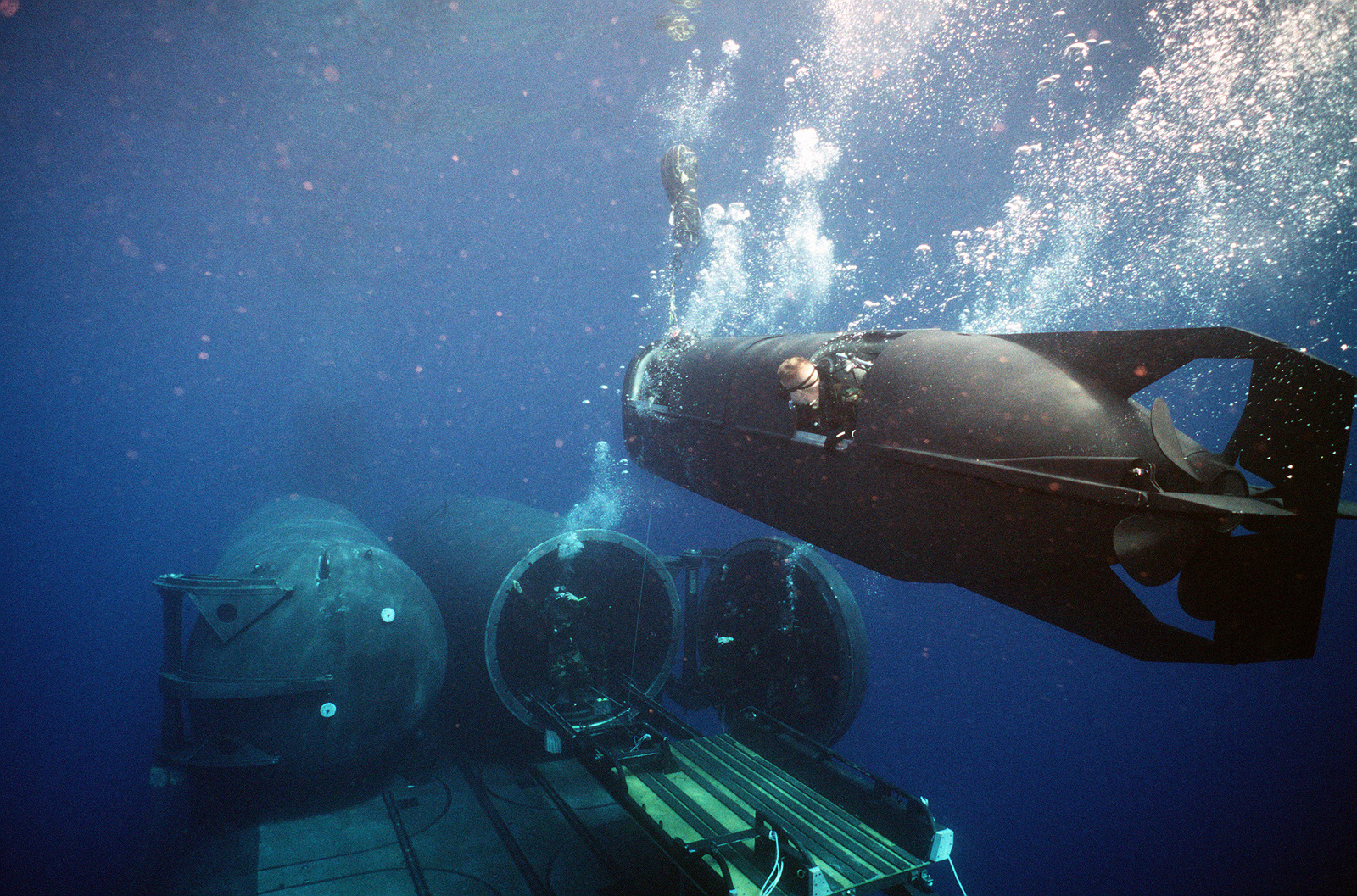 Drydock shelter (DDS) deck captain signals to the operator of a Mark 8 special dive vehicle (