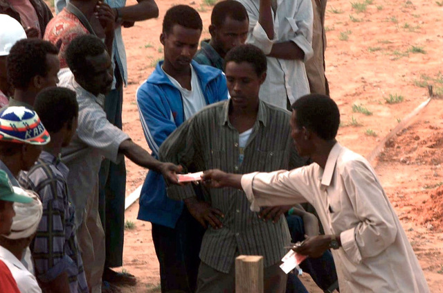 """High angle shot looking down on a Somali clan representative, right, handing out work passes to clan members who were granted permission to work on Sword Base, Mogadishu, Somalia. An agreement has been reached between Sword Base personnel and """"non-aggressive"""" clam leaders. It states that an equal amount of members from each clan will be allowed to work at Sword Base on any given day. This mission is in direct support of Operation RESTORE HOPE"""