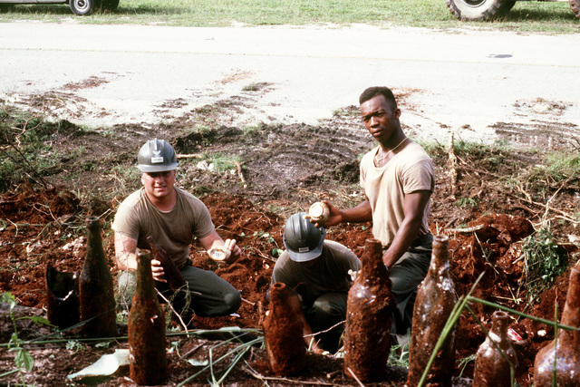 (Left to right) Builder Third Class (BU3) David Bevier, MASTER at Arms First Class (MA1) Rick Garza and Construction Electrician Constructionman (CECN) Richard Daniel, all from Navy Mobile Contruction Battalion 3 (NMCB-3), retrieve World War Two artifacts and bottles from the jungle overgrowth near the old Japanese prisoner of war camp area on Orote Point, Naval Station Guam. The work is being done in preparation for next year's observation of the 50th anniversary of Guam's WWII liberation