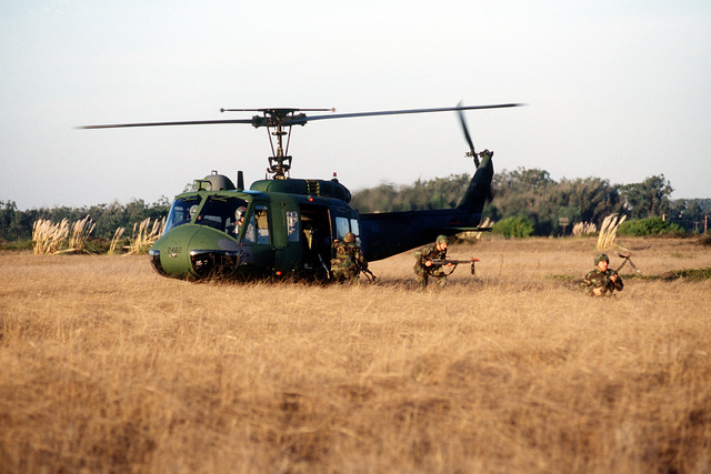 Security police personnel, carrying M-16 rifles equipped with MILES gear (multiple independent laser engagement system), exit a UH-1 Iroquois helicopter onto an open field during exercise Olympic Flag 93-3. The exercise brings security police together with missileers, maintainers, and civil engineers to help the nations' ICBM force increase comb at readiness