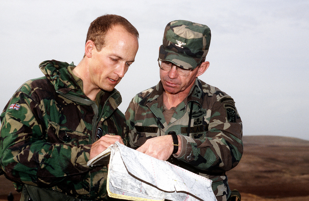 Squadron Leader Russell W. La Forte (left), Military Coordination Center (MCC) security officer, Royal Air Force Regiment, High Wycombe, UK, and COL. Jerald L. Thompson, co-commander of the MCC, Fort Bragg, NC, pin-point their location on a map in northern Iraq. They are northwest of Iraqi military camp, Faydah, about one kilometer from the edge of the security allied zone. The MCC is the Joint Service Combined Forward Liaison element to Joint Task Force Provide Comfort, which is based at Incirlik Air Base, Turkey. Their mission is to monitor Iraqi compliance with the United Nations Security Council resolution 688. The MCC is staffed by military representatives from Turkey, Britain, ...