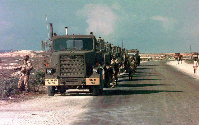 Straight on front view of a row of US Army M915 Series Tractors lined up along the side of the road. They are from the 594th Transportation Company, Fort Campbell, Kentucky, and are at Rabbit Base, which is the Indian troop's base camp next to Mogadishu airport. The tractors will hook up to Indian trailers and move them to the new Indian camp at Baidoa, Somalia. This mission is in direct support of Operation Restore Hope