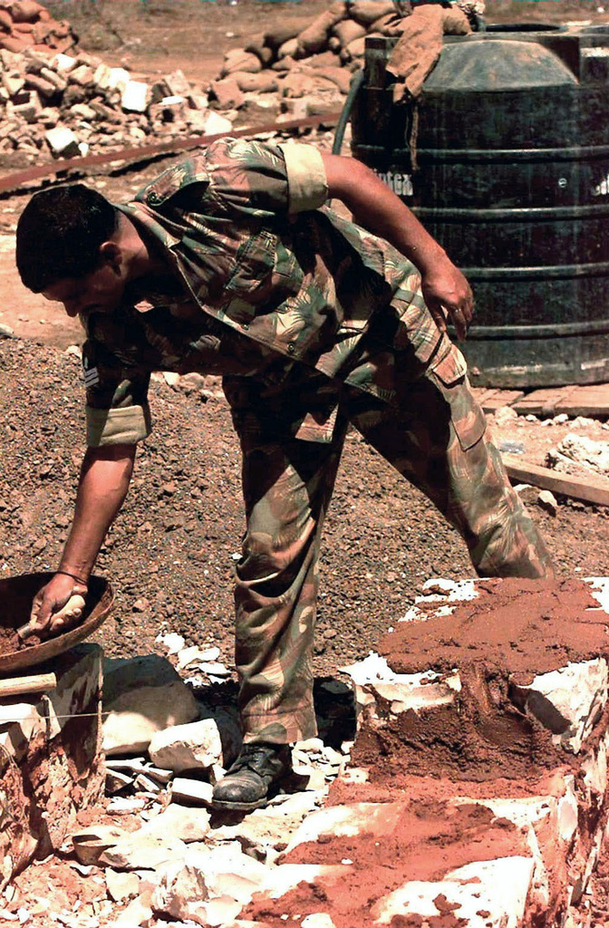 Straight on shot of a Soldier from the Indian Army bent over and reaching with his right hand for some cement. He is applying the concrete to a foundation being built at a well site. The Indians drilled the well in order to provide the United Nations members and the humanitarian relief organizations with fresh water to wash and drink. This mission is in direct support of Operation Restore Hope