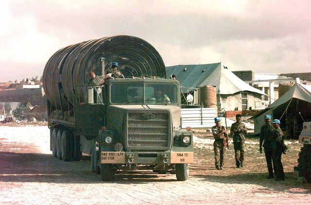 Straight on shot of a US Army M915 Series Tractors from the 594th Transportation Company, Fort Campbell, Kentucky, pulling a trailer of water tanks belonging to the Indian Army. Indian Soldiers stand at the right watching US Army SPC Roach drives the tractor-trailer out of the old base at Mogadishu Airport and will deliver it to the Indian Army's new base in Baidoa, Somalia. This mission is in direct support of Operation Restore Hope