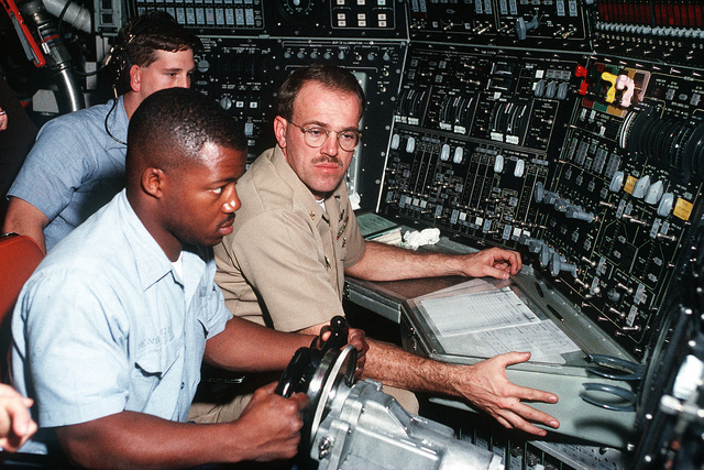 The chief of the watch, CHIEF Machinist Mate (MMC) Scott L. Davidson oversees the diving of the ballistic missile submarine USS NEBRASKA (SSBN-739). At the stern planesman position, Yeoman Second Class (YN2) Ervin F. Renwick guides the 18,700 ton boat below the waves