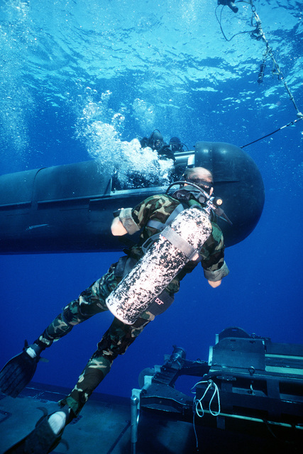 The drydock shelter (DDS) deck captain passes wet notes to the Mark 8 special dive vehicle (SDV) navigator prior to the SDV launch from the nuclear-powered submarine USS KAMEHAMEHA (SSN-642) during duel shelter special operations training off the coast of Oahu, Hawaii
