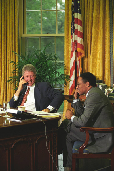 Photograph of President William J. Clinton and Secretary of Agriculture Mike Espy on Telephones in the Oval Office