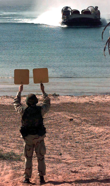 A member of the BMU1/Landing Craft Air Cushion (LCAC) Team stands back to camera and holds two marshaling placards high over his head. In the distance a LCAC approaches Blue Beach. The LCAC, which is capable of speeds of over 40 knots and loads of 60 tons, came on shore with supplies used to support Operation Show Care. This operation is in direct support of Operation Restore Hope