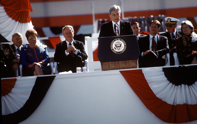 """Virginia's U.S. Senator John W. Warner, a former Secretary of the Navy, speaks of the aircraft carrier as """"a symbol of America's commitment"""" to the gathered crowd of 16,000 during the christening ceremony of the Nimitz class nuclear-powered aircraft carrier John C. Stennis (CVN-74) at the Newport News Ship Building and Dry Dock Corporation"""