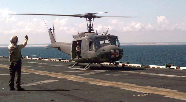 A flight deck crewmember from the Iwo Jima Class Amphibious Assault Ship, USS NEW ORLEANS LPH 11, stands back to camera and gives a thumbs up to a US Army UH-1N Huey Medical Evacuation Helicopter that has just touched down onto the deck of the NEW ORLEANS during a joint service mass casualty exercise held 18 November 1993. The 46th Medical Task Force conducted the exercise with members of the US Marines and Navy to determine what actions will be taken in the event of a mass casualty situation during Operation Continue Hope in Mogadishu, Somalia