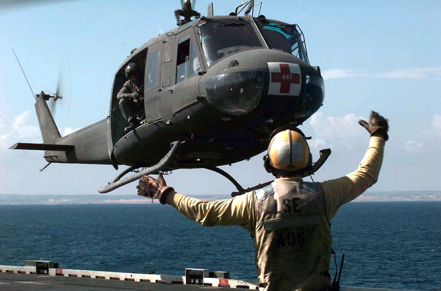 A flight deck crewmember from the Iwo Jima Class Amphibious Assault Ship, USS NEW ORLEANS LPH 11, stands back to camera and marshals in a US Army UH-1N Huey Medical Evacuation Helicopter on the deck of the NEW ORLEANS during a joint service mass casualty exercise held 18 November 1993. The 46th Medical Task Force conducted the exercise with members of the US Marines and Navy to determine what actions will be taken in the event of a mass casualty situation during Operation Continue Hope in Mogadishu, Somalia