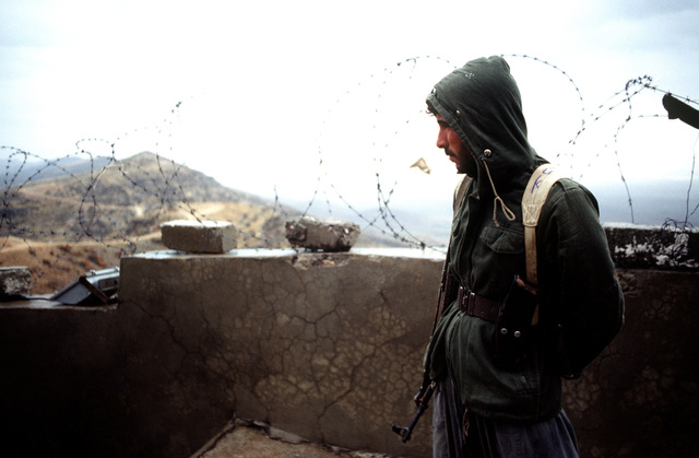 A Kurdish guard stands watch on a hill overlooking the city of Zakhu in northern Iraq