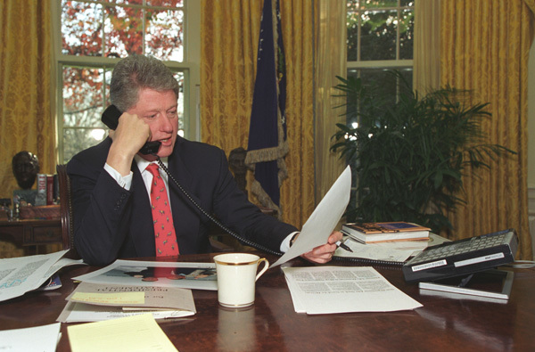 Photograph of President William Jefferson Clinton Speaking on the Telephone in the Oval Office of the White House in Washington, D.C.