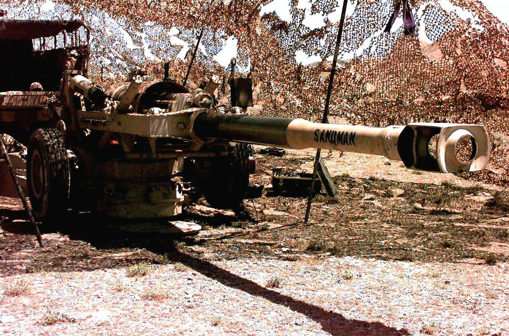 Right side front view of a M198, 155mm Tow Howitzer assigned to Charlie, 1ST of the 11th Artillery, Camp Pendleton, California. The howitzer sits under a Camouflage netting at RANGE-6, south of Mogadishu, Somalia. This mission is in direct support of Operation Restore Hope