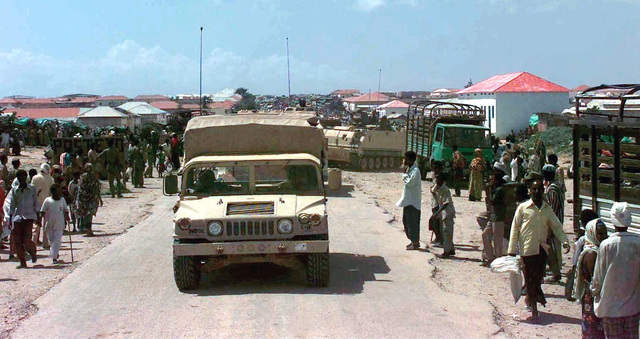 A convoy of US Army M9998 High-Mobility Multipurpose Wheeled Vehicle (HMMWV) and M113A3 Armored Personnel Carriers from the 1ST of the 64th Mechanized, Fort Stewart, Georgia, traveling from Victory Base, Mogadishu, Somalia, to the old airfield north of Mogadishu. The convoy passes by a Somali market. The vehicles are used to provide support for Operation More Care. This operation provided the people of Mogadishu with basic medical and dental care from 2 to 4 Dec. 1993. More Care is in direct support of Operation Restore Hope