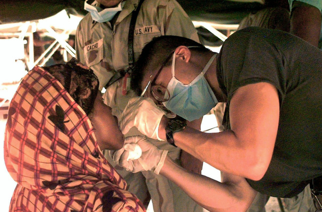 """A Somali woman, left, is having her teeth cleaned by US Navy LT Loren Masuoka, a dental officer from the USS America (ship not shown). US Army and Navy personnel (not shown) arrived at """"Old Port"""" Mogadishu, Somalia, to participate in a Medical/Dental Civil Action Program. They provided basic health and dental care needs to Somalis in the surrounding area. LT Masuoka, a 5 year Navy veteran, is 31 years old and from Portland, Oregon. This mission is in direct support of Operation Restore Hope"""