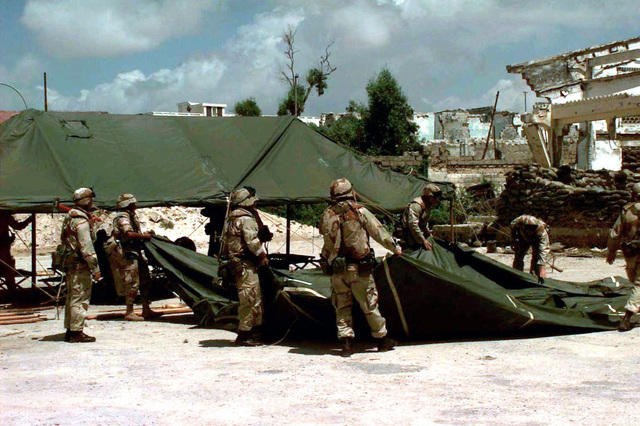 """Seven US Marines are shown unfolding canvas tent material. US Army and Navy personnel (not shown) arrived at """"Old Port"""" Mogadishu, Somalia, to participate in a Medical/Dental Civil Action Program. They provided basic health and dental care needs to Somalis in the surrounding area. This mission is in direct support of Operation Restore Hope"""