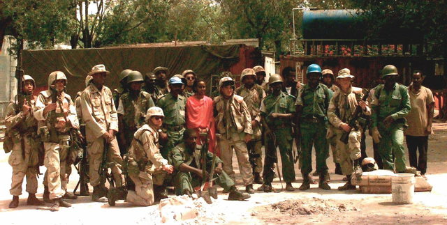 Straight on shot of a group of people posing for a picture. US Marine LT Ron Stevens, front and center, with black goggles on his Kevlar helmet, from the 13th Marine Expeditionary Unit, poses with US Marine and Nigerian Army Engineers at the Restore Hope Orphanage in Mogadishu, Somalia. The joint effort by the Soldiers repaired the roof of the orphanage (not shown) in preparation for the upcoming rainy season. The orphanage is the home for about 1800 Somali orphans ranging from infants to mid-teens. Stevens, a three-year USMC veteran, is 28 years old and if from Los Angeles, California. This mission is in direct support of Operation Restore Hope