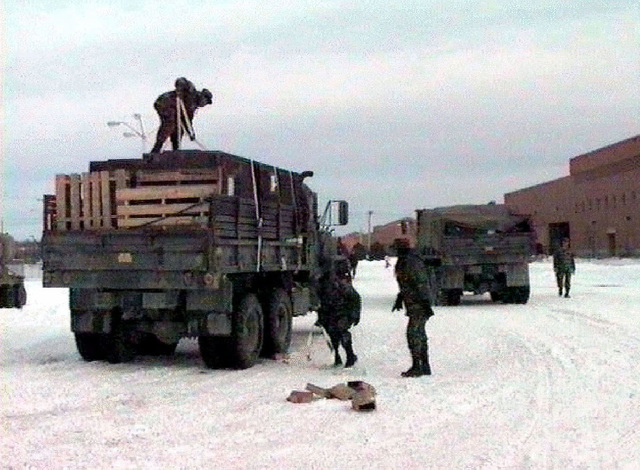 Medium shot, rear view of two US Army 5-ton Cargo trucks being loaded with material by four Soldiers. Snow is on the ground at Fort Drum, New York. A line of red brick buildings is seen at the right side of the frame. This mission is in support of Operation Restore Hope