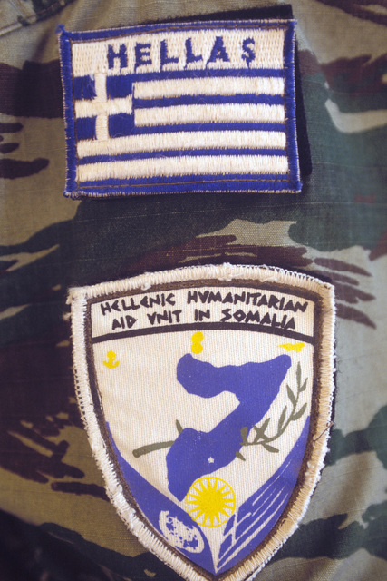 The Patch on a Greek Soldier's shoulder identify his nationality and his mission. The top patch represents the Hellenic Army and the bottom patch signifies his humanitarian aid role in Somalia