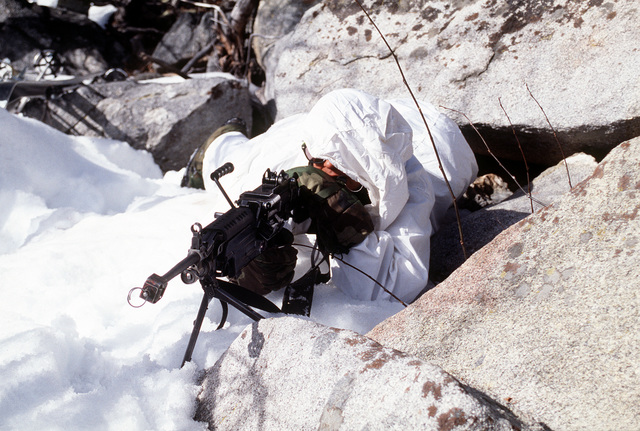 A Marine automatic rifleman from India Company, Third Battalion, Eighth Marines lies prone and ready to fire an M249 Squad Automatic Weapon. His weapon is equipped with a blank firing apparatus and bipod. The Marine is covered between large snow covered rocks while on an ambush patrol. His is aimed at the kill zone during cold weather training at Silver Creek