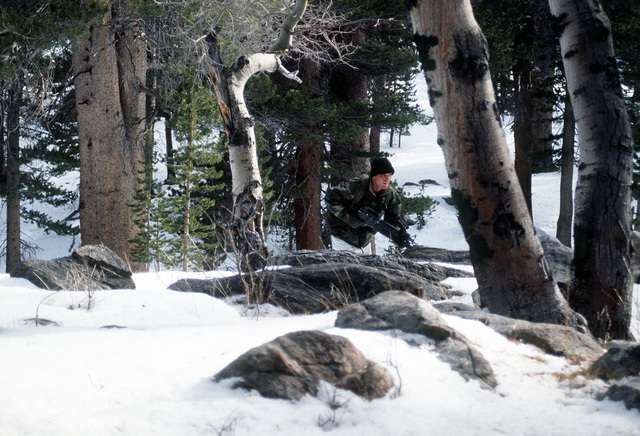 A Marine rifleman from India Company, Third Battalion, Eighth Marines runs for cover through the snow covered rocky woodland of Silver Creek during cold weather training