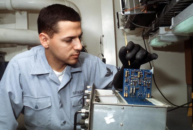Electronics Technician Second Class (ET2) Jaime Gonzalez calibrates a circuit board in a piece of radar equipment on board the destroyer tender USS CAPE COD (AD-43)