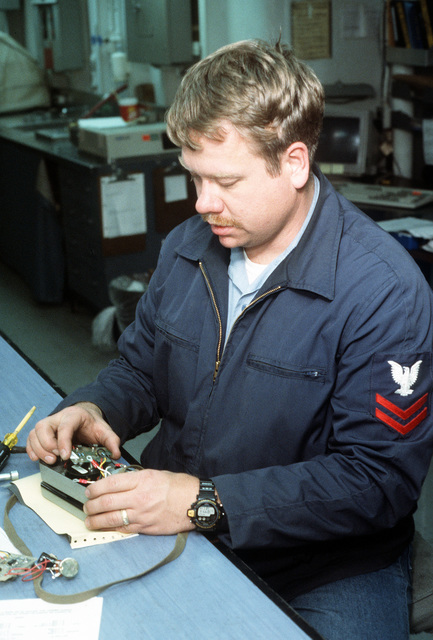 Instrumentman Second Class (IM2) Rickie Shannon replaces a circuit board in the combustible gas indicator on board the destroyer tender USS CAPE COD (AD-43)