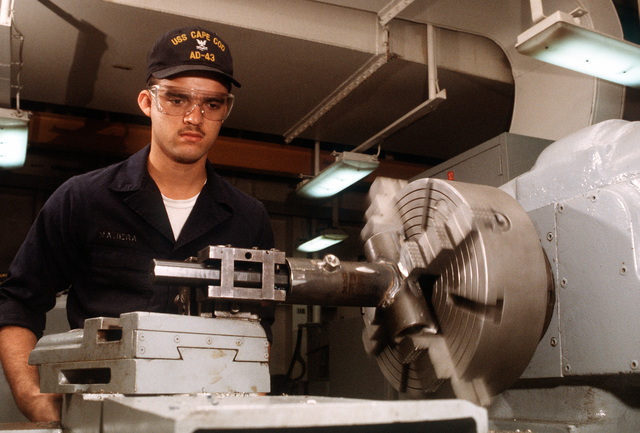 Machine Repairman Second Class (MM2) Jesus Gallard expands the inside diameter of a piping joint using a machine lathe in the machine shop on board the destroyer tender USS CAPE COD (AD-43)