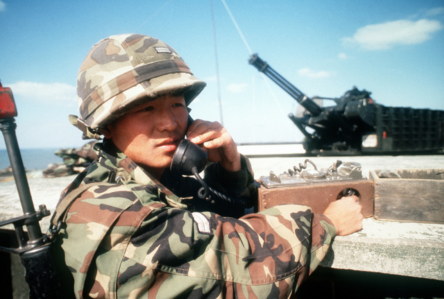 SGT Lee Hyunltun, a member of the ROK Army, and exercise participant talks on his field phone from the top of Big Coyote at Kunsan Air Base. A Vulcan gun is in the background. Exact Date Shot Unknown